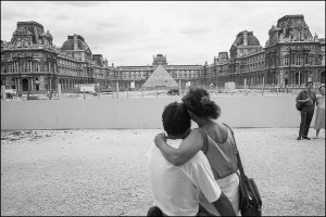 Couple enlaced looking afar at the Pyramide du Louvre black and white photograph