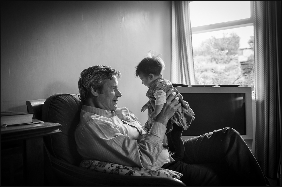 a black and white photograph of a man holding his grandchild