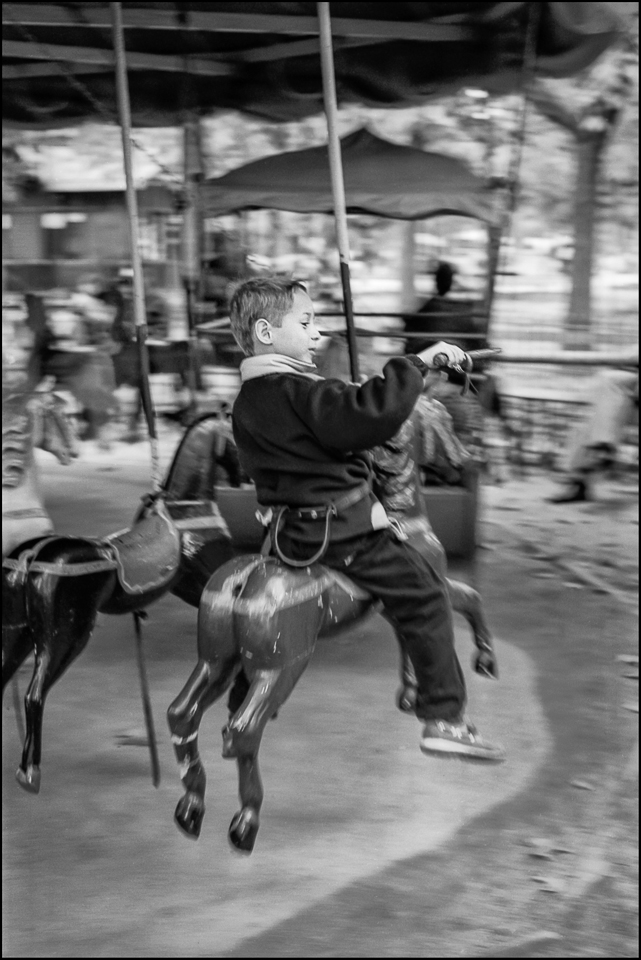 Black and white photograph of a child on a merry go round