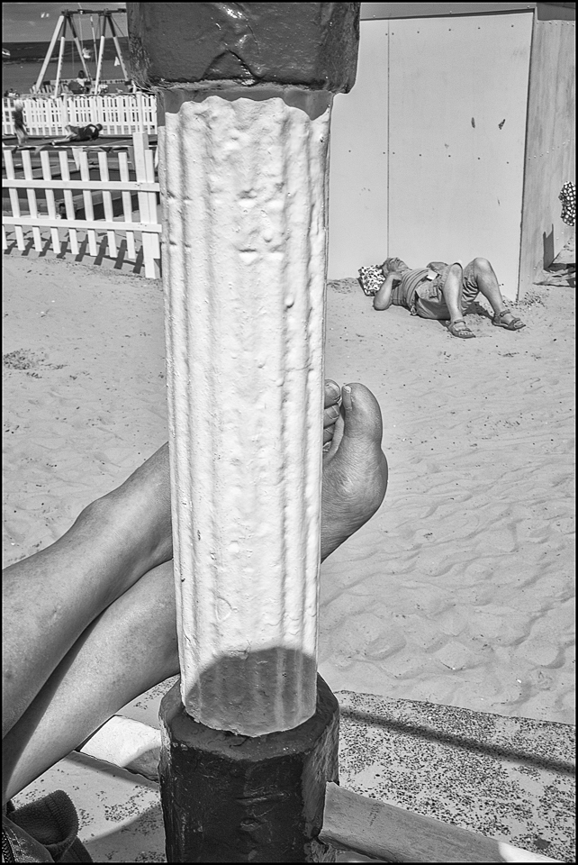 black and white photograph of feet in the sun along the beach at Weymouth UK