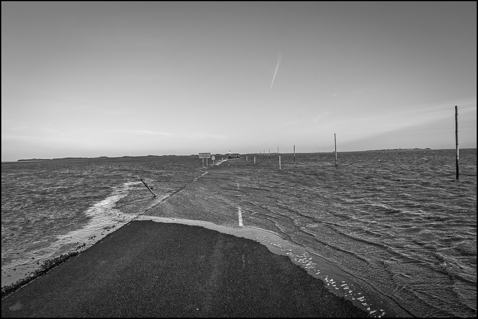 black and white photograph of tide coming in on holy Island causeway