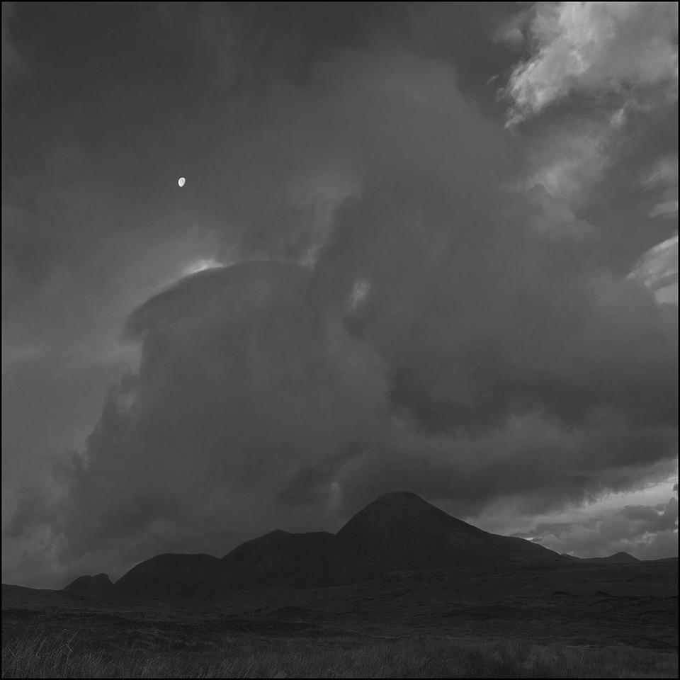 black and white landscape photograph of the moon and clouds over Skye
