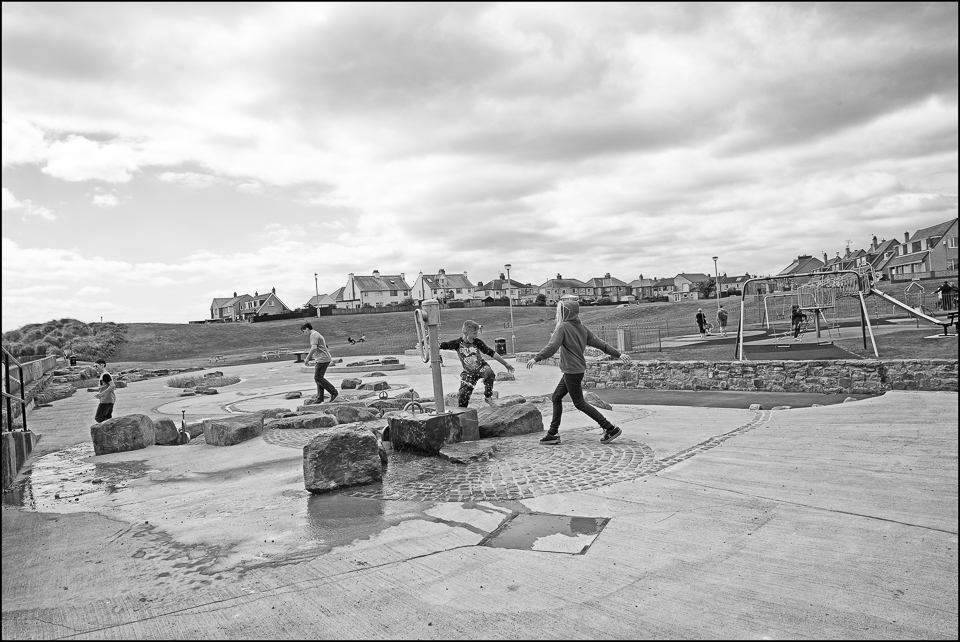 kids playing Amble Northumberland black and white photograph by Christophe Chevaugeon